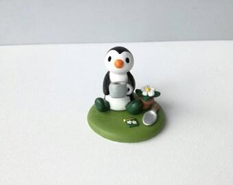Gardening penguin gift. Pottery penguin in the garden in wellies. Miniature gardening penguin and daisy ornament