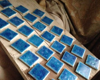 28 Vintage tiles with faience style glaze.