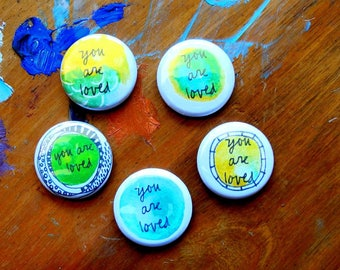 you are loved button with pin back - blue + green - single blessing button
