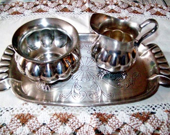 A silver plated milk jug, sugar bowl and tray