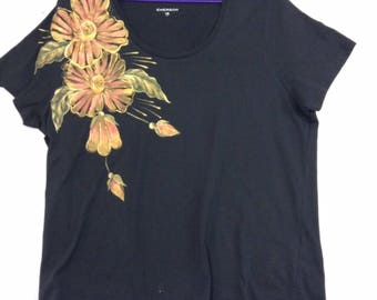 Black t-shirt with painted daises on right shoulder.
