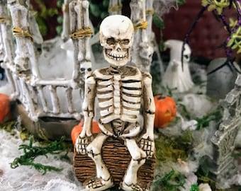 Miniature Skeleton Sitting on a Log