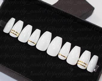 White nails with gold tape accents