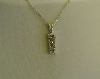 A Silvertone Bar Pendant with Faux Diamonds