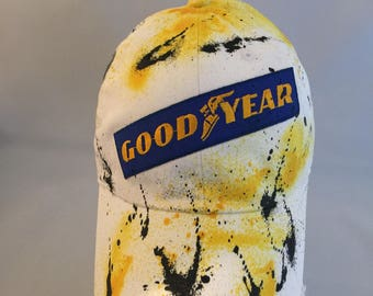 White with yellow and black paint splatter good year dad hat