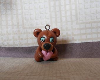 Brown bear with blue eyes, holding a pink heart