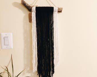 black & white wall hanging on tree branch