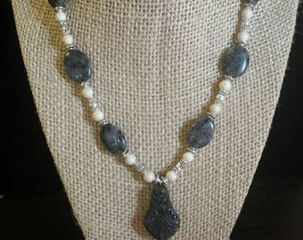 Fossil bead and black marble with carved pendent
