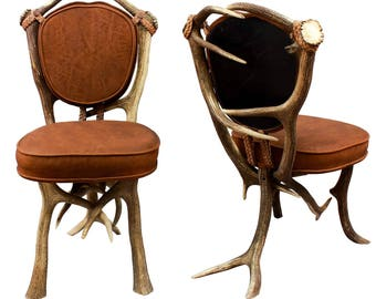 a pair of vintage lodge style antler chairs
