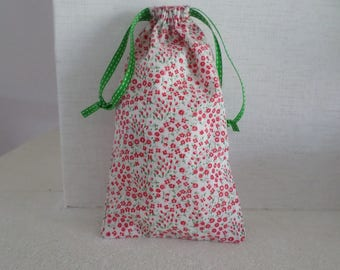 pouch made in a fabric filled with red flowers on white background