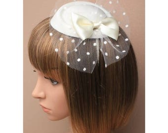 Cream pillbox fascinator with satin bow and spotted cream net on a satin fabric aliceb and. Ideal for special occasions weddings and races.