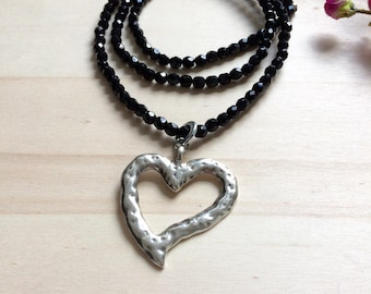 Necklace has beads, hollow heart pendant