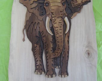 Inlay in relief of an elephant. item made of poplar wood