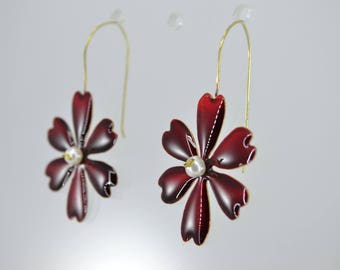 flowers of brass colored with red cold enamel and pearl in the center