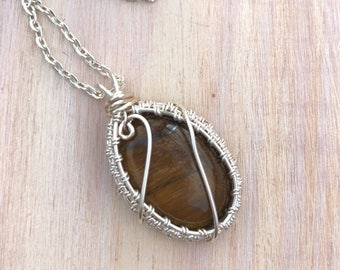 Wire wrapped tiger's eye pendant necklace - silver plated wire woven around an oval tiger's eye pendant on a silver plated chain