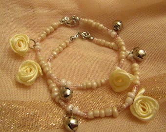 Pink beaded bracelet with cream fabric roses and bell accessories