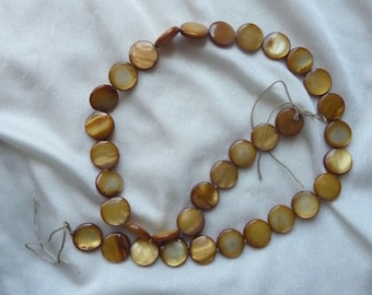 Bead, Mother of Pearl, Shell, Dyed, Dark Gold, 10mm Flat Coin, Sold per 15 inch strand. There are 35 beads on the strand.