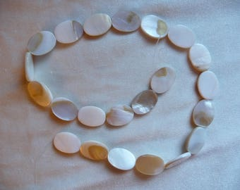 Bead, Mother-of-pearl shell (natural / bleached), white, 10x6mm-16x12mm flat oval. Sold per 15 inch strand.