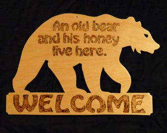 An old bear and his honey live here - Welcome sign