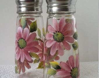 Set of two salt and pepper shakers hand painted with pink daisies.