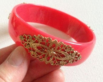 Bangle - decorated pink plastic bangle decorated with a gold embellishments