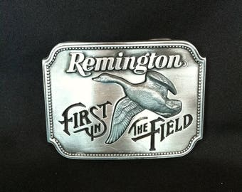 """A Small Belt Buckle That Reads Remington First In The Field """"Canada Goose"""" Sid Bell 1980"""