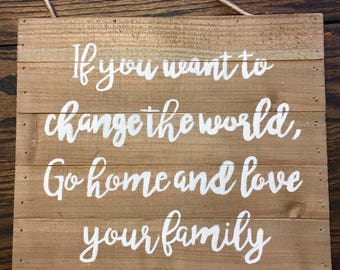 "Hand painted wooden sign, ""If you want to change the world, go home and love your family"""
