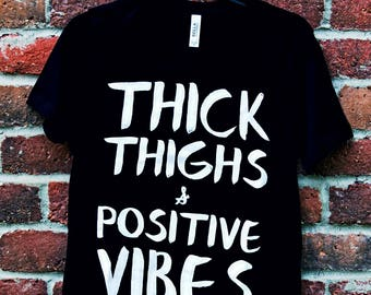 Thick Thighs & Positive Vibes available in women's black fitted crew neck T shirts and razor back tanks!