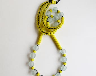 Long beaded necklace with yellow matte and transparent Native American glass crow beads and light blue Ghanian beads on black leather cord