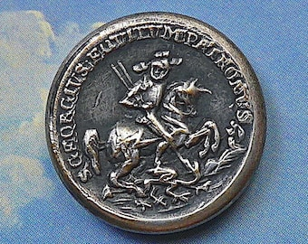 St. George button, antique.   Pressed tinted metal featuring St. George slaying the Dragon, metal loop shank. c 19th. century.