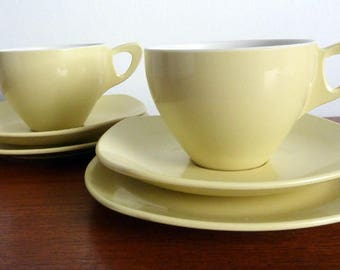 A Pair of Vintage Midwinter Modern Yellow Break Resistant Cup, Saucer, Plate Trios