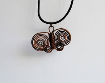 Boho style dainty butterfly pendant necklace made from antique bronze copper wire hung on a black leather cord