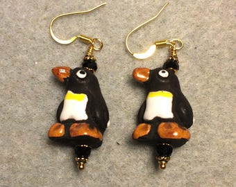 Black, brown and white ceramic penguin bead earrings adorned with black Chinese crystal beads.