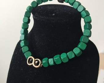 Green beaded bracelet with gold infinity charm