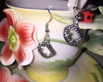 Sterling silver hooked vampire teeth charmed dangle earrings.
