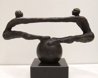sculpture of 2 characters balancing on a ball