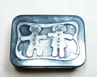 Gingerbread cookie cutters. 4 in this tin by Metzke from 1977. Metzke hinged tin with cookie cutters. 2 ginger bread figures grace the top