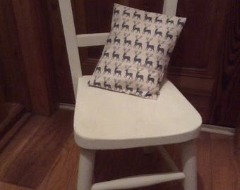 Antique child's chair trimmed with little cushion with reindeer print