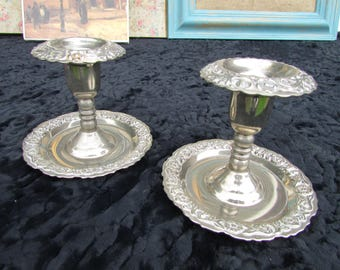 A pair of small white metal candle holders.