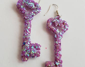 Sparkly pink key earrings made from wood and covered in glitter.