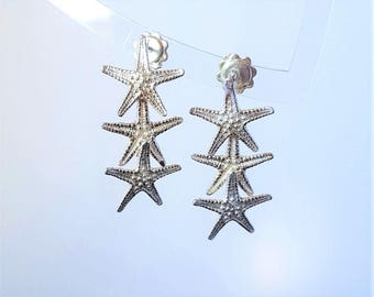 Silver earrings with three small starfish