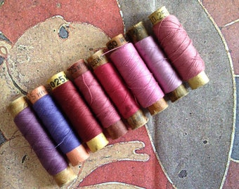 Spools of threads set. Vintage organic cotton 8 threads spools in pink-purple colors.