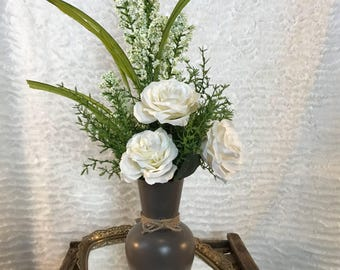 Artificial floral arrangement featuring white Roses, greenery, and tall white accent spray in a painted glass vase