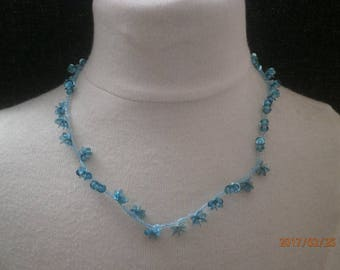 Beaded necklace and blue and turquoise glitter.