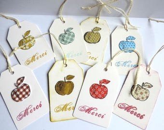 """MERCI"" tags with multicolored apples"