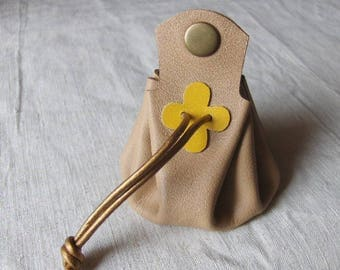 Coin purse is beige leather with yellow clover
