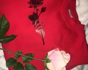 Red crewneck jumper with hand holding rose design