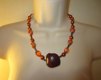 Orange pendant necklace in seed pod of Creeper