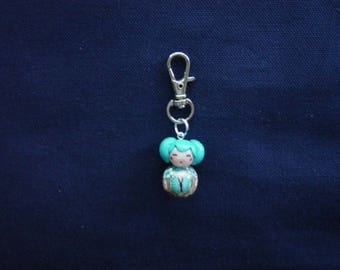 Turquoise Kokeshi Keychain Butterfly light brown background
