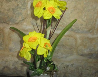 Artificial flower arrangement with daffodils in a clay pot.
